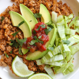 This easy skillet dinner combines ground turkey taco meat with cauliflower rice topped with lettuce, avocado and salsa for an easy, low-carb weeknight meal!