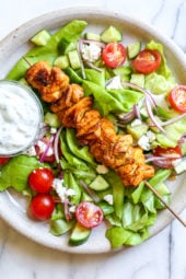 This Mediterranean inspired salad is made with Grilled Chicken Shawarma kebabs served over salad with Feta and Tzatziki.