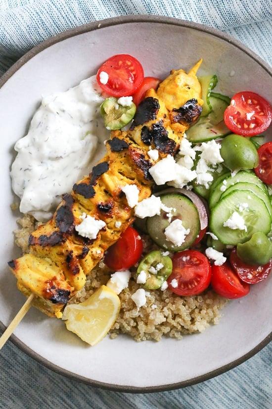Pollo a la parrilla marinado con yogurt ahumado servido sobre quinua y tomates, pepinos y aceitunas de inspiración mediterránea con tzatziki y queso feta.