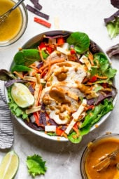 Grilled Chicken Salad with greens and vegetables are tossed in a honey-lime vinaigrette and topped with a delicious peanut sauce.