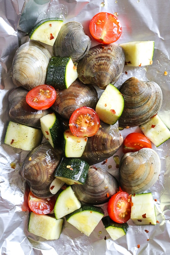 Grilled little neck clams cooked in foil packets with zucchini and tomatoes in a garlic white wine sauce, so fast and easy, perfect to make all summer long!