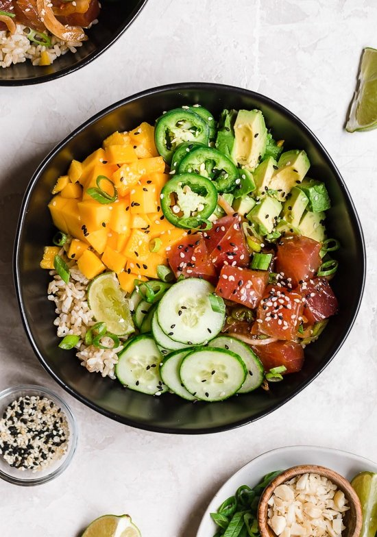 Hawaiian Poke Bowl made with marinated tuna, brown rice, avocado, cucumber, mango, macadamias and scallions.