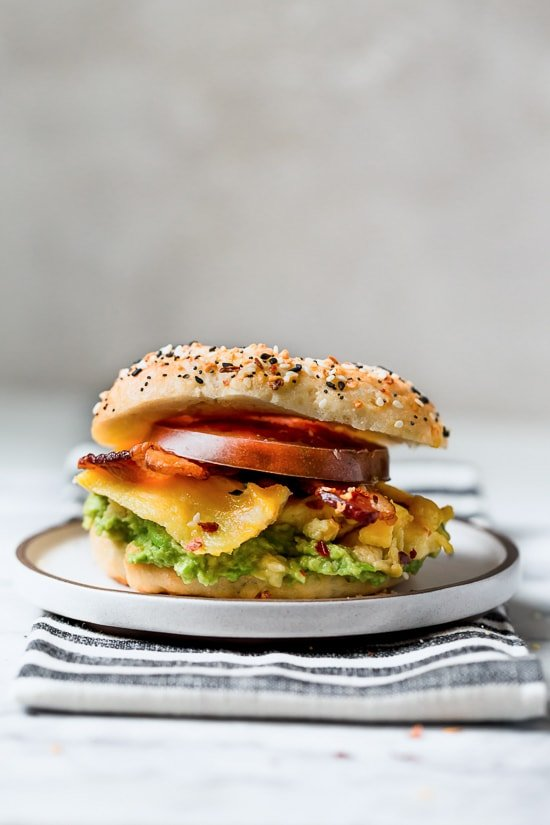 Bacon, egg and avocado on a bagel is my favorite breakfast sandwich made with scrambled eggs, center cut bacon and sliced tomatoes on my homemade bagels.