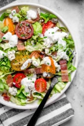 Classic wedge salad meets chopped salad in this easy side salad dish made with lettuce, bacon, tomatoes, blue cheese and chives with a light homemade blue cheese dressing.