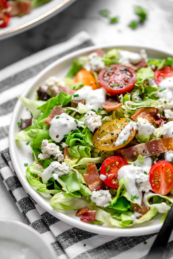 Classic wedge salad meets chopped salad in this easy side salad dish made with lettuce, bacon, blue cheese and chives with a light homemade blue cheese dressing.