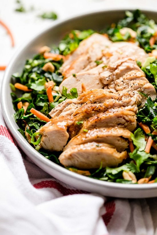 Houston's (Lightened-Up) Kale Salad with Peanut Vinaigrette is satisfying, made with a combo of grilled chicken, kale, cabbage, carrots, peanuts, scallions, cilantro and mint tossed in a light peanut-sesame dressing.