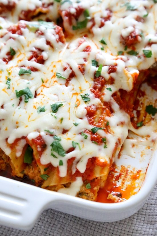 This easy no-boil baked manicotti pasta dish, known as Cannelloni is stuffed with ricotta, parmesan, mozzarella and lean ground beef, then covered in sauce and cheese. Perfect for the holidays, for to bring to a potluck or to enjoy any night of the week!