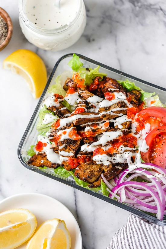 Halal Food Cart inspired chicken served over a big salad of lettuce and tomatoes drizzled with a yummy white yogurt sauce.
