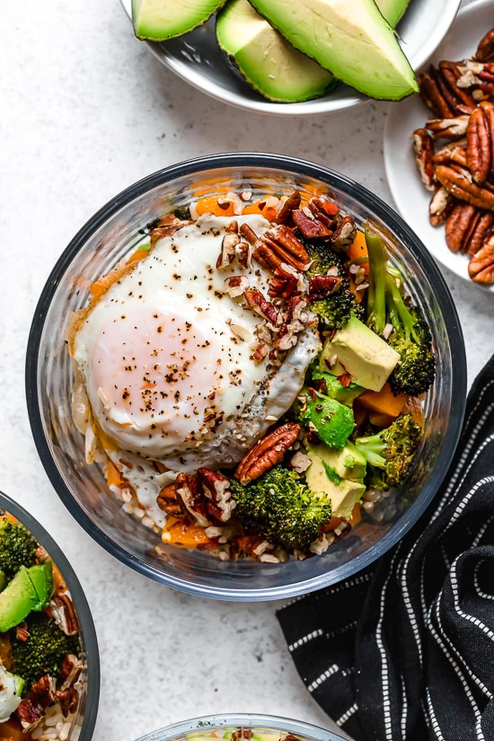 This easy Buddha Bowl is made with roasted broccoli, butternut squash, and onions piled on top of whole grain rice and topped with sliced avocado, a sunny-side fried egg, and crunchy pecans.