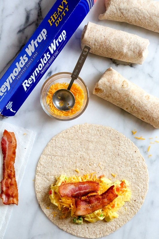 These freezer burritos, stuffed with scrambled eggs, scallions, bell pepper, bacon and cheese, are a great way to start the day! Make them ahead and freeze them for meal prep so you can have them ready any day of the week.