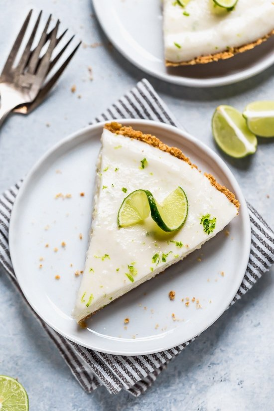 This easy Key Lime Yogurt Pie is a cross between a key lime pie and a key lime cheesecake with a light, creamy filling that is sweet and tart, made with key lime juice, yogurt and cream cheese in a graham cracker crust.