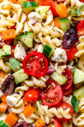 Greek Pasta Salad is light and fresh, loaded with garden tomatoes, bell peppers and cucumbers tossed in a homemade Greek dressing with Kalamata olives and Feta cheese. Perfect for summer parties!