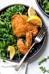 Crisp, golden, delicious Air Fryer Chicken Milanese with Baby Arugula and lemon wedges is one of my favorite dinner recipes!