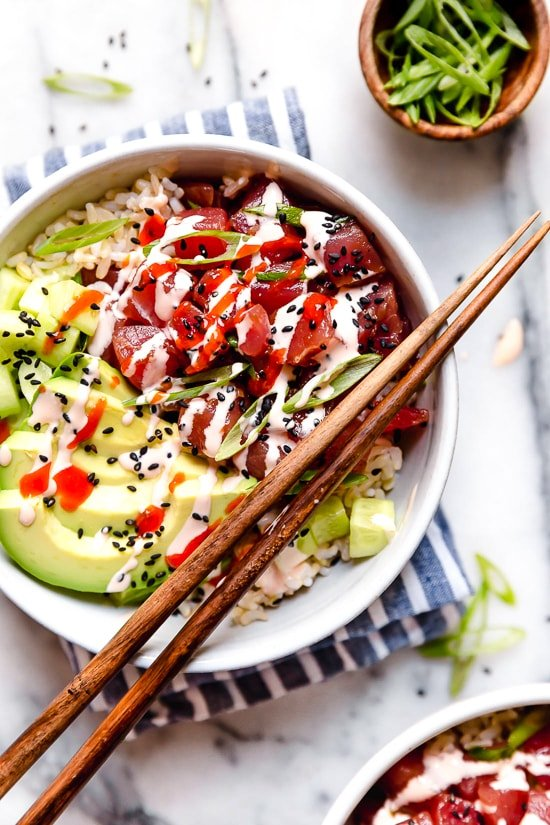 Spicy Tuna Poke Bowls made with chunks of fresh tuna, avocado, cucumbers, spicy mayo, scallions cut on the bias served on a bed of steamed rice.