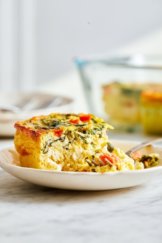 This easy Breakfast Casserole recipe is made with eggs, spinach, tomatoes and Feta cheese and only takes a few minutes to whip up. You can make it ahead of time, so it's the perfect breakfast egg casserole for Christmas morning or any day!