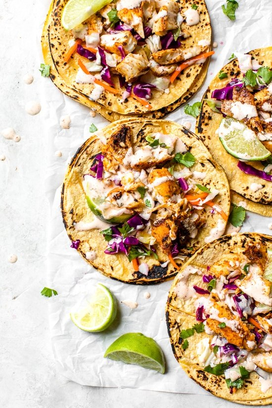 This easy, healthy fish taco recipe is made with cod seasoned with a chili-lime cumin rub topped with slaw – no breading, no frying!