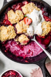 Skillet Mixed Berry Buttermilk Cobbler is made with blackberries, raspberries, and strawberries covered with a delicious biscuit topping and baked in a cast iron skillet.