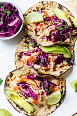 These easy Slow Cooker Chicken Tacos made in the crock pot with chicken breast, salsa, and spices are on repeat in my house!