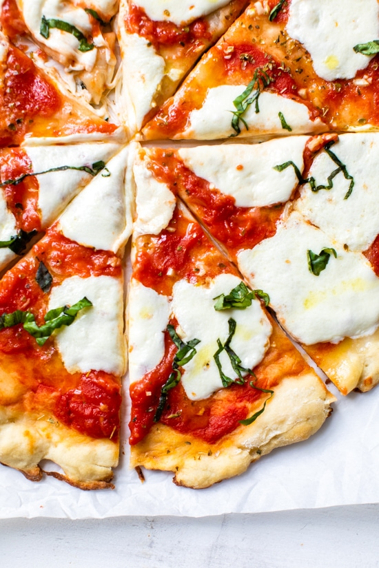 Easy Margherita Pizza made from scratch with my yeast-free, thin crust pizza dough topped with a simple raw tomato sauce, fresh mozzarella cheese, and basil.