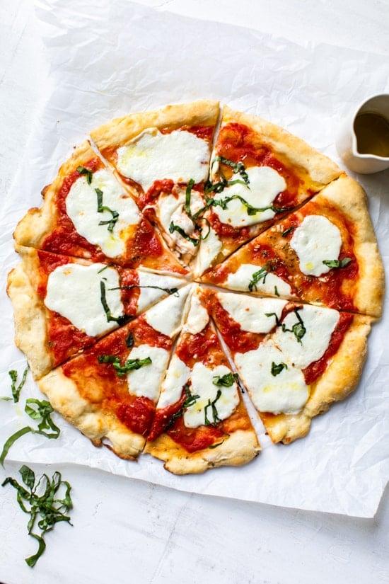 "Fácil Pizza Margherita hecha desde cero con mi masa de pizza de masa fina y sin levadura cubierta con una simple salsa de tomate cruda, queso mozzarella fresco y albahaca. ""Ancho ="" 550 ""altura ="" 825 ""data-pin-description ="" Fácil Margherita Pizza hecha desde cero con mi masa de pizza de masa fina, sin levadura, cubierta con una simple salsa de tomate cruda, queso mozzarella fresco y albahaca. #pizza #pizzadough #noyeastpizza ""data-pin-title ="" Margarita Pizza ""srcset ="" https://www.skinnytaste.com/wp-content/uploads/2020/05/Margherita-Pizza-1-5.jpg 550w , https://www.skinnytaste.com/wp-content/uploads/2020/05/Margherita-Pizza-1-5-500x750.jpg 500w, https://www.skinnytaste.com/wp-content/uploads/ 2020/05 / Margherita-Pizza-1-5-170x255.jpg 170w, https://www.skinnytaste.com/wp-content/uploads/2020/05/Margherita-Pizza-1-5-260x390.jpg 260w, https://www.skinnytaste.com/wp-content/uploads/2020/05/Margherita-Pizza-1-5-150x225.jpg 150w ""tamaños ="" (ancho máximo: 550px) 100vw, 550px ""/></noscript><img class="