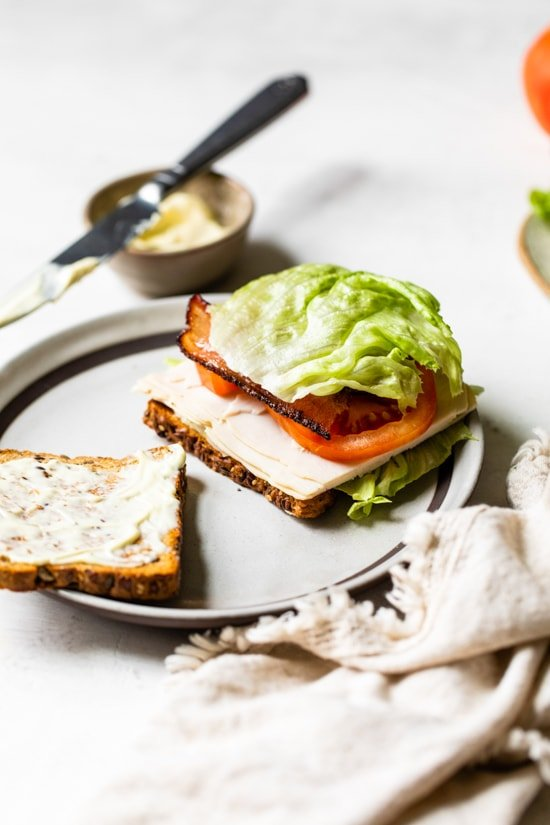 A classic Turkey Club sandwich made healthy, piled high with turkey breast, bacon, lettuce, and tomato on whole grain bread, the perfect easy lunch.