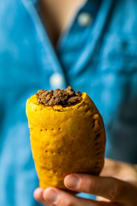 Girl holding a Jamaican Beef Patty