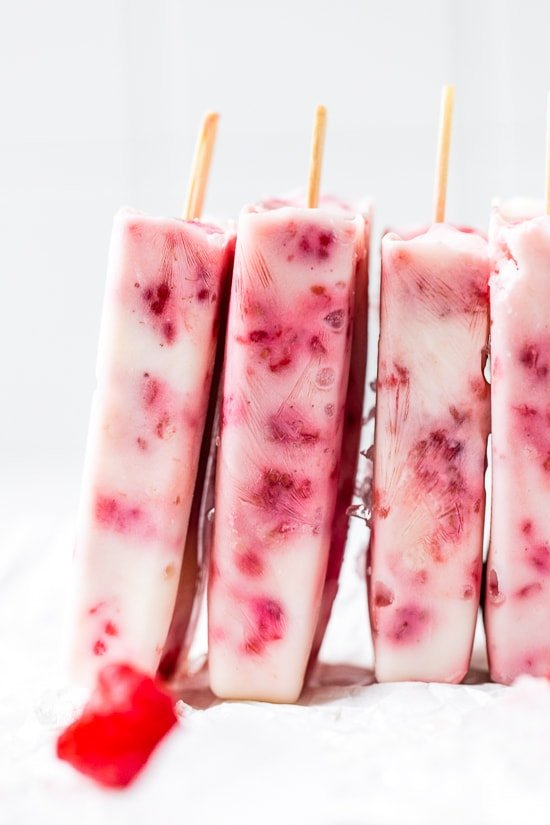 Raspberry Yogurt Ice Pops stacked on a white background.