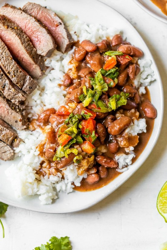Dominican Beans over rice with aji picante on top and steak on the side.