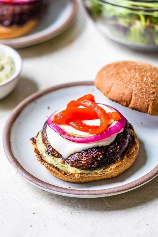 Esses hambúrgueres grelhados com cogumelos Portobello com cobertura de mussarela, pimentão vermelho e pesto de maionese são deliciosos e uma excelente opção de hambúrguer vegetariano.