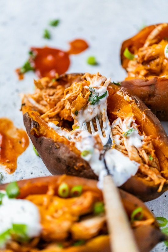 Slow Cooker Chicken Enchilada Stuffed Sweet Potatoes with a fork and sour cream.