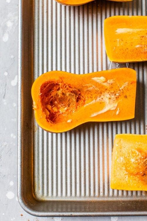 cut open honeynut squash on a sheet pan.