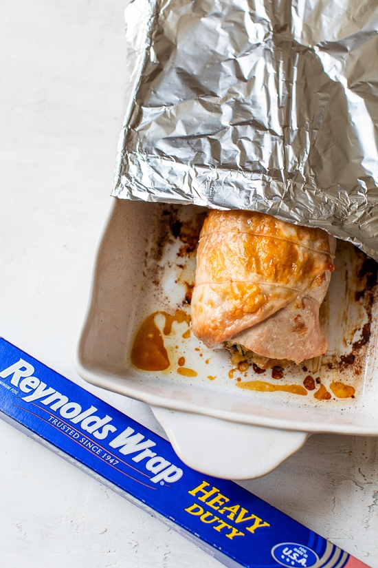 Turkey breast in a baking dish with foil.