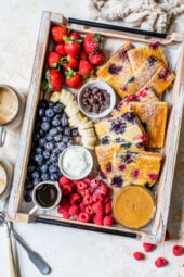 sheet pan pancakes on a try with berries and toppings.