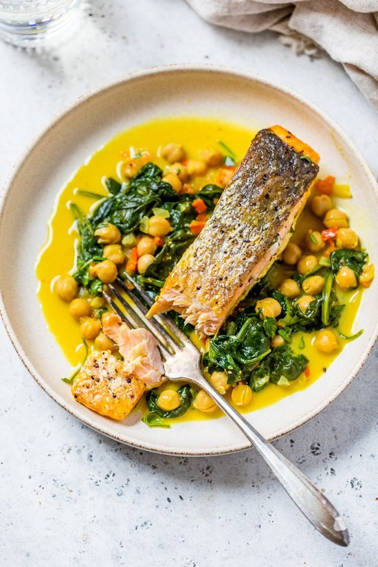 salmon on a plate with a fork, spinach and chickpeas