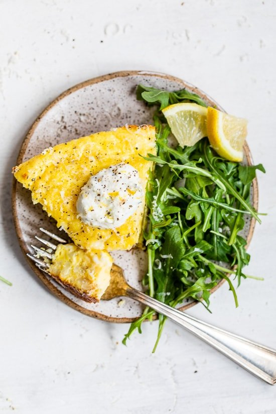 This creamy and delicious Cacio e Pepe Frittata is a fun twist on the Italian classic pasta dish. A protein- packed breakfast, lunch or dinner made with roasted cauliflower, Greek yogurt, eggs, and Parmesan served with a dollop of lemony yogurt and arugula salad.