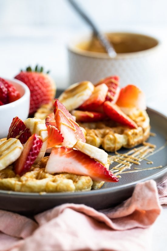 Oat waffles with strawberries, peanut butter and bananas.