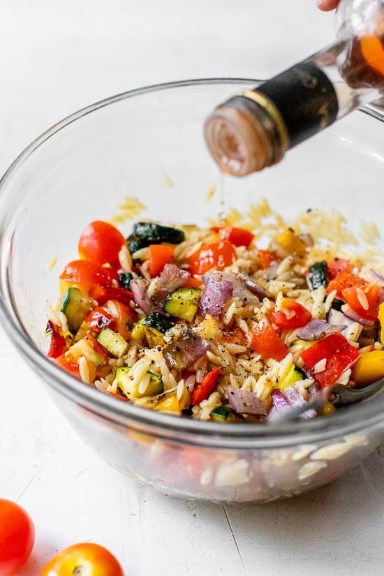 adding red wine vinegar to pasta salad