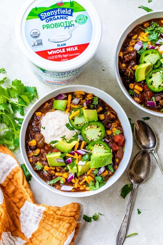 Black Bean Vegetarische Chili gegarneerd met yoghurt, jalapenos, kaas en avocado.